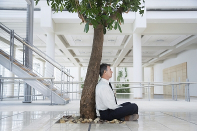 Full length side view of middle aged businessman meditating unde